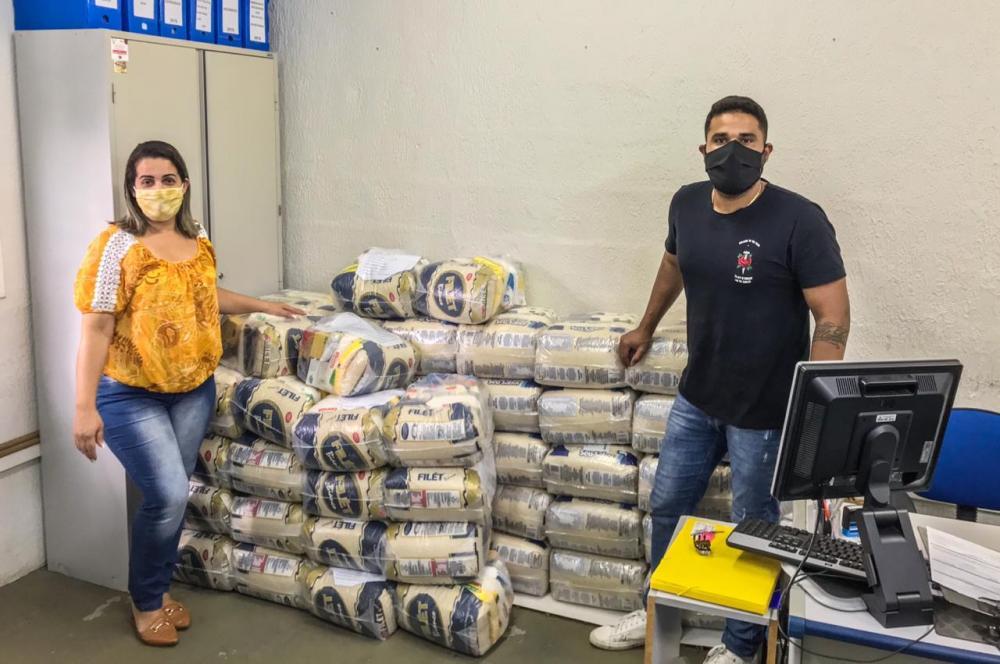 A secretária de Desenvolvimento Social e Trabalho, Rosilene Filipe Matos, e o cantor Léo Mai durante a entrega dos alimentos